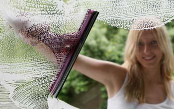 Tjej från städfirma Malmö som tvättar fönster